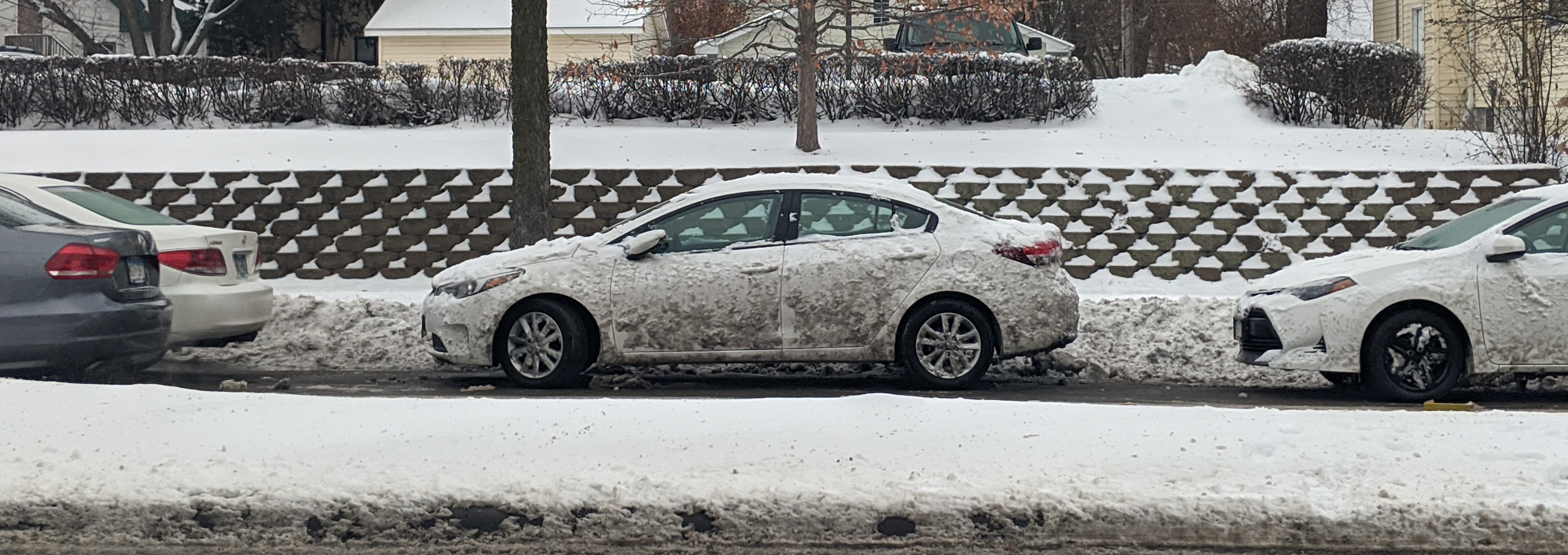 A once-white car, covered in snow and muck.